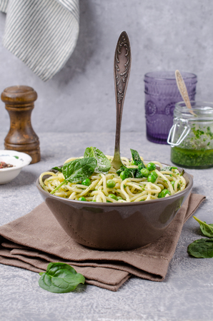 Spaghetti with vegetables, pesto and cheese in a dish on a slate background. Selective focus. Standard-Bild - 121034560