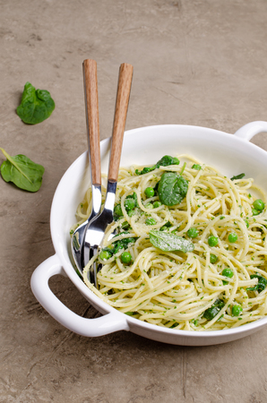 Spaghetti with vegetables, pesto and cheese in a dish on a slate background. Selective focus. Standard-Bild - 121034562