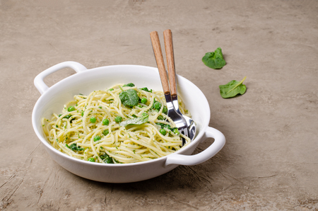 Spaghetti with vegetables, pesto and cheese in a dish on a slate background. Selective focus. Standard-Bild - 121034563