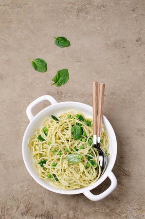 Spaghetti with vegetables, pesto and cheese in a dish on a slate background. Selective focus. Standard-Bild - 121034566