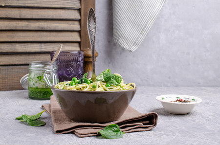 Spaghetti with vegetables, pesto and cheese in a dish on a slate background. Selective focus. Standard-Bild - 121034568