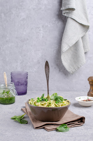 Spaghetti with vegetables, pesto and cheese in a dish on a slate background. Selective focus. Standard-Bild - 121034571
