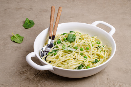 Spaghetti with vegetables, pesto and cheese in a dish on a slate background. Selective focus. Standard-Bild - 121034573