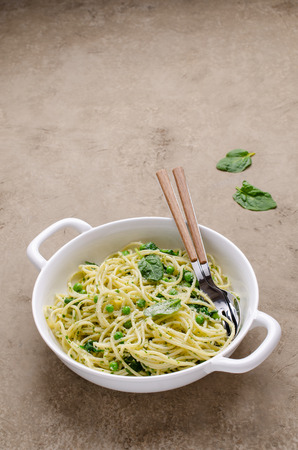Spaghetti with vegetables, pesto and cheese in a dish on a slate background. Selective focus. Standard-Bild - 121034574