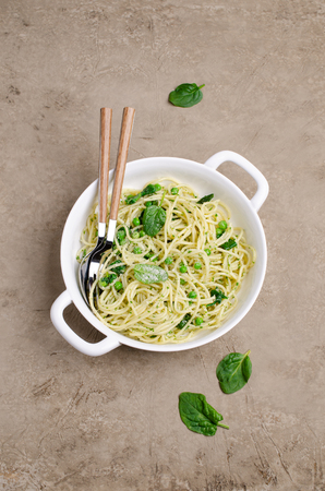 Spaghetti with vegetables, pesto and cheese in a dish on a slate background. Selective focus. Standard-Bild - 121034576