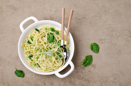 Spaghetti with vegetables, pesto and cheese in a dish on a slate background. Selective focus. Standard-Bild - 121034577