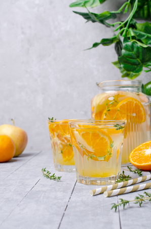 Infused water with fruit and thyme in glass on wooden background. Selective focus. Standard-Bild - 121034582