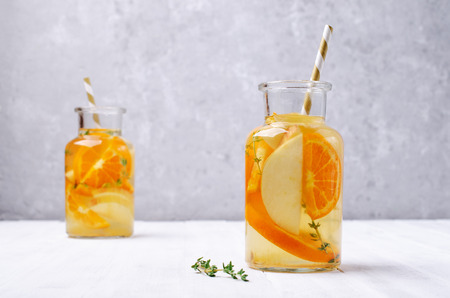 Infused water with fruit and thyme in glass on wooden background. Selective focus. Standard-Bild - 121034585