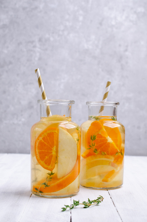 Infused water with fruit and thyme in glass on wooden background. Selective focus. Standard-Bild - 121034586