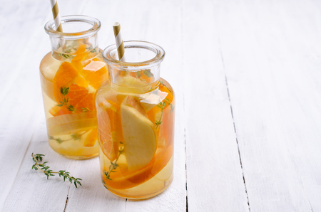 Infused water with fruit and thyme in glass on wooden background. Selective focus. Standard-Bild - 121034599