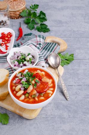 Gęsta zupa jarzynowa z makaronem i fasolą w naczyniu na drewnianym tle. Selektywne skupienie. Zdjęcie Seryjne