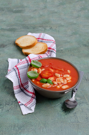 Thick tomato soup with beans in a bowl on the table. Selective focus. Imagens - 121858316