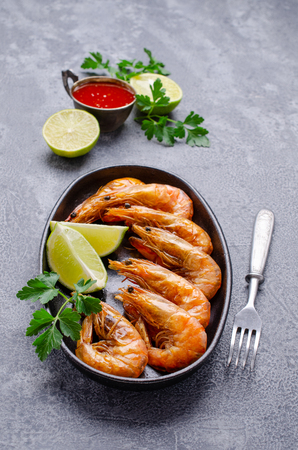 Large fried shrimp with citrus and tomato sauce on a slate background. Selective focus. Stock Photo