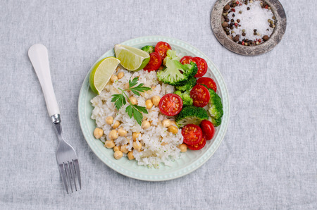 White fried rice with vegetables in a dish on a textile background. Selective focus. Banque d'images