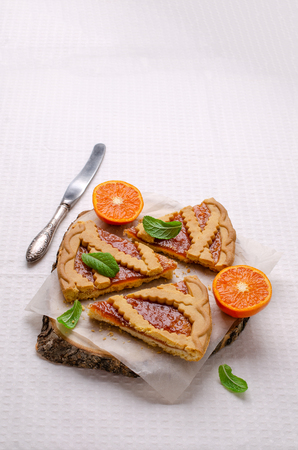 Pieces of sweet cake with jam and clementines on a light textile background. Selective focus. Zdjęcie Seryjne - 122312891