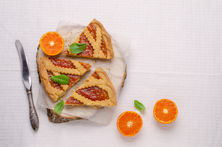Pieces of sweet cake with jam and clementines on a light textile background. Selective focus.