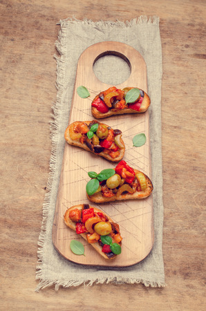 Bruschetta with stewed vegetables and Basil on a wooden background. Selective focus. Stock fotó