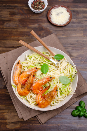 Spaghetti with zucchini and fried shrimp on a brown wooden background. Selective focus.