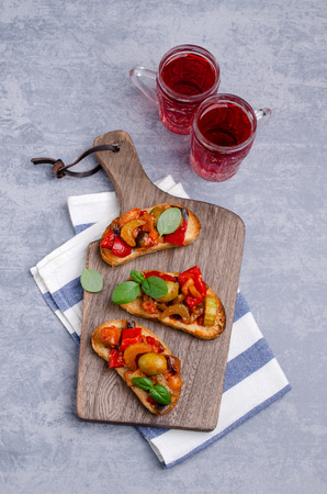 Bruschetta with stewed vegetables and Basil on a wooden background. Selective focus. Foto de archivo