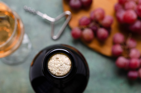 Cork in a bottle of wine on the background of large grapes on slate. Selective focus. Imagens