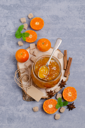 Orange marmalade with peel and spices in a glass jar on a wooden background. Selective focus. Stock fotó