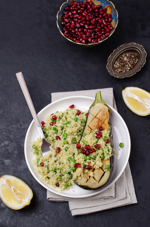 Fried eggplant with couscous and pomegranate seeds in a bowl on a slate background. Selective focus.