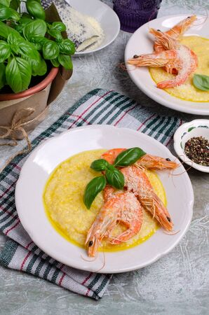 Large untreated shrimp with polenta in a dish on a slate background. Selective focu
