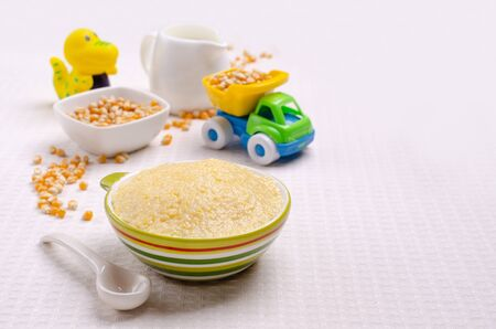 Corn baby porridge in a ceramic dish on a textile background. Selective focus. Stock Photo