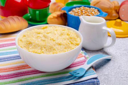 Corn baby porridge in a ceramic dish on a slate background. Selective focus.