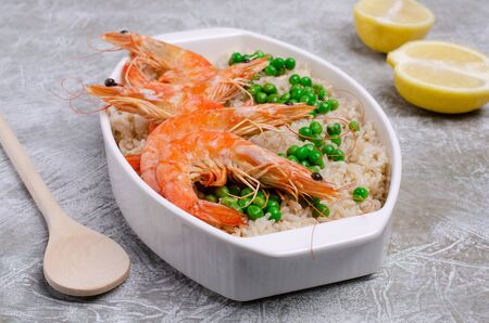Whole shrimp with brown rice in a dish on a slate background. Selective focus.