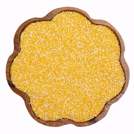 Organic corn grits in a dish on a white background. Design concept.