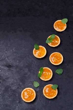 Tartlets with orange jam and mint on a slate background. Selective focus.