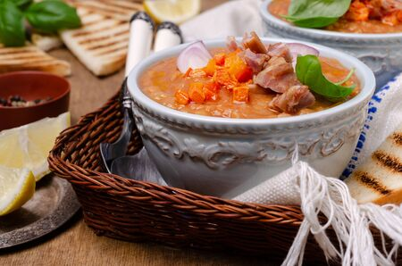 Thick soup with lentils, slices of meat and vegetables in a dish on a wooden background. Selective focus.
