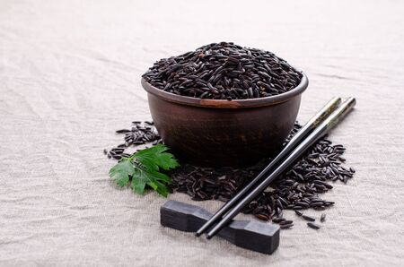 Black unpolished rice in ceramic bowl on textile background. Selective focus.