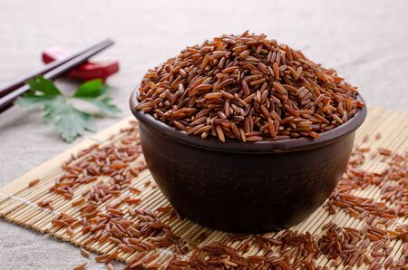 Red unpolished rice in ceramic bowl on textile background. Selective focus. Standard-Bild