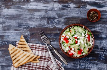 Fresh vegetable salad with cottage cheese in ceramic dish on wooden background. Selective focus. Imagens