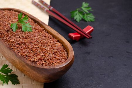 Red unpolished rice in a wooden bowl on a slate background. Selective focus.