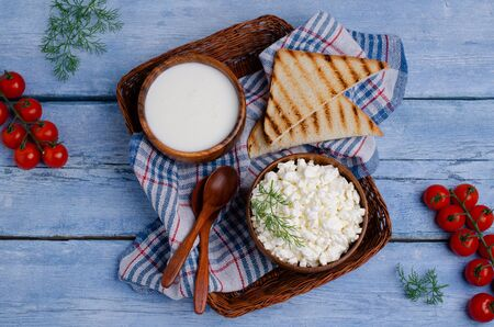 Granulated white cottage cheese with vegetables and sour cream in a dish on a wooden background. Selective focus.