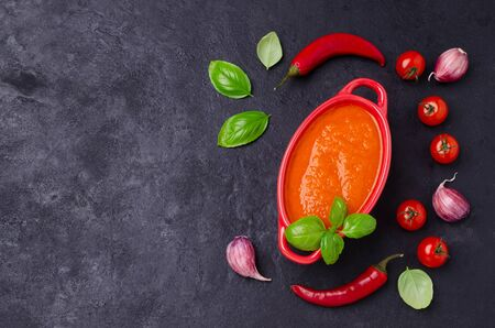 Homemade vegetable red sauce in ceramic bowl on black slate background. Selective focus.