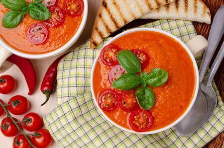 Zuppa di crema di verdure rossa fatta in casa con fette di pomodori fritti e basilico su fondo di legno. Messa a fuoco selettiva.