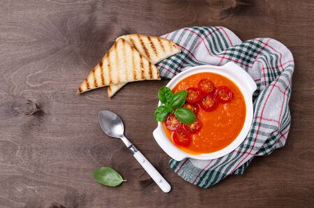 Homemade vegetable red cream soup with slices of fried tomatoes and Basil on a wooden background. Selective focus.