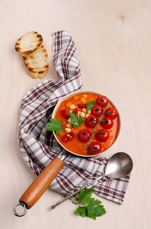 Red vegetable soup with chickpeas and parsley in a dish on a wooden background. Selective focus.