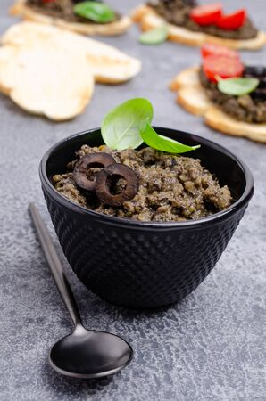 Traditional black tapenade with fried bread and tomatoes on slate background. Selective focus.