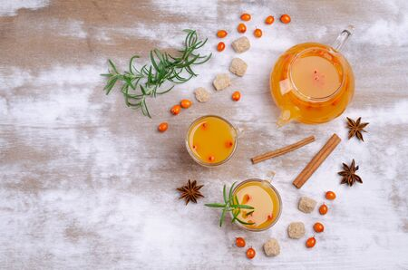 Vitamin healthy sea buckthorn tea in glass with spices on a wooden background. Selective focus.