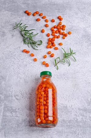 Sea buckthorn infused water in glass with rosemary branches on a slate background. Selective focus. 스톡 콘텐츠