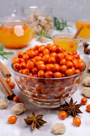 Raw sea buckthorn berries in a glass dish on a wooden background with spices. Selective focus.