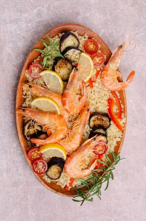 Unpeeled boiled shrimp with bulgur and vegetables in a dish on a slate background. Selective focus. Stock fotó