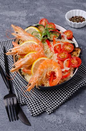Unpeeled boiled shrimp with bulgur and vegetables in a dish on a slate background. Selective focus. Stockfoto