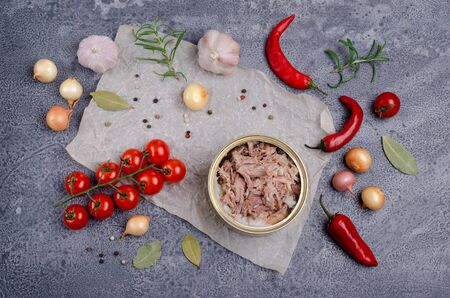 Canned meat in metal with vegetables and spices on a slate background. Selective focus.