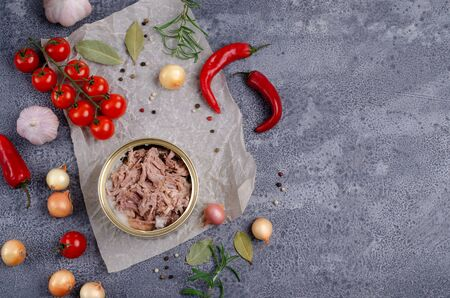 Canned meat in metal with vegetables and spices on a slate background. Selective focus. Stock Photo